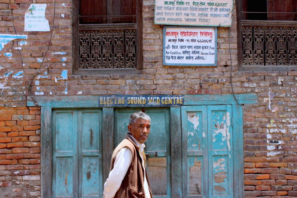 Gli uomini se non riposano passeggiano, lui davanti all'Electro-Sound VCD Centre