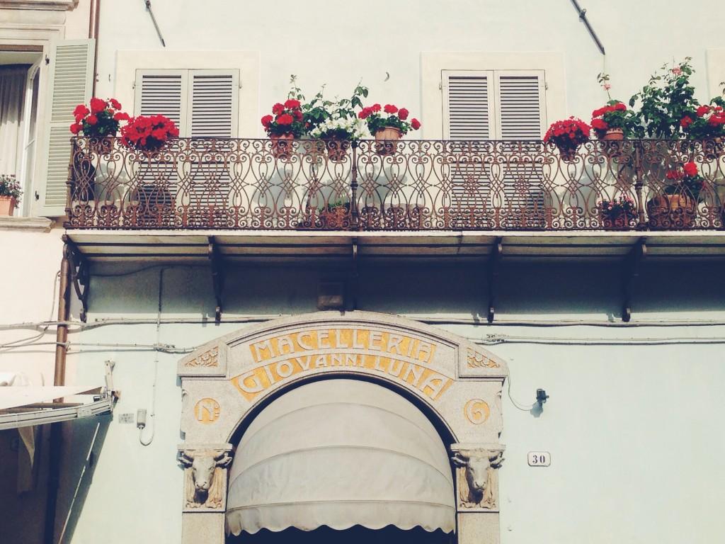 Macelleria Giovanni Luna, fiori colorati e balconi ghirigorosi