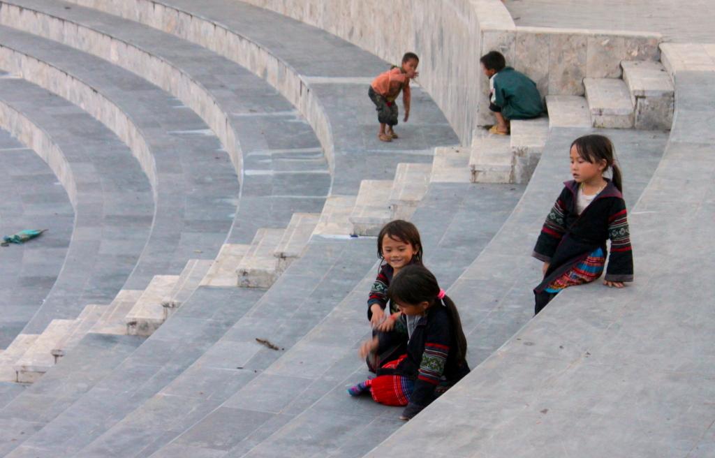 Tanti piccoli Black H'mong giocano nella piazzetta di Sapa prima che diventi buio