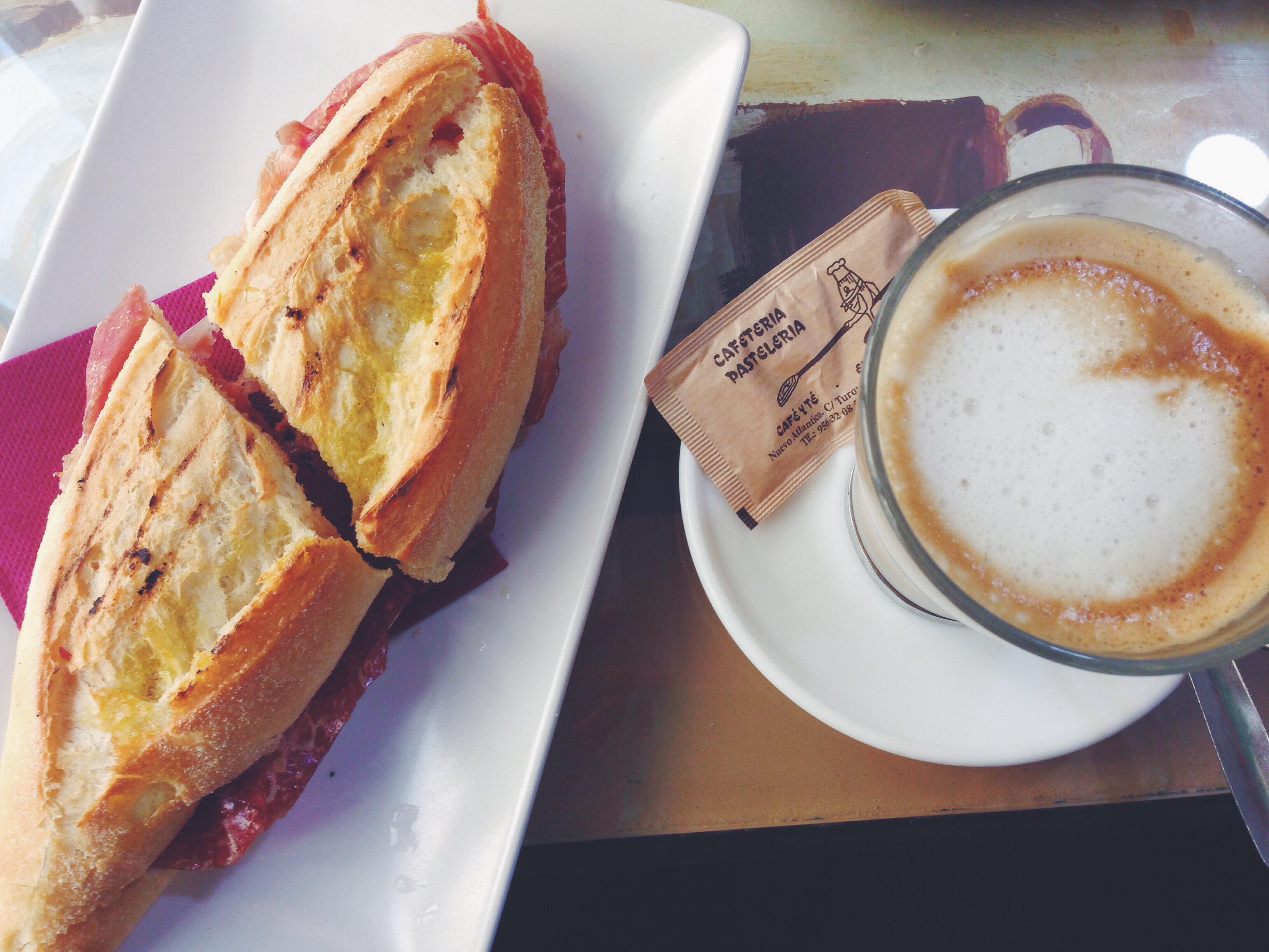 La colazione andalusa: un cafècon leche e un Montesierra con olio, salsa di pomodoro e jamon serrano