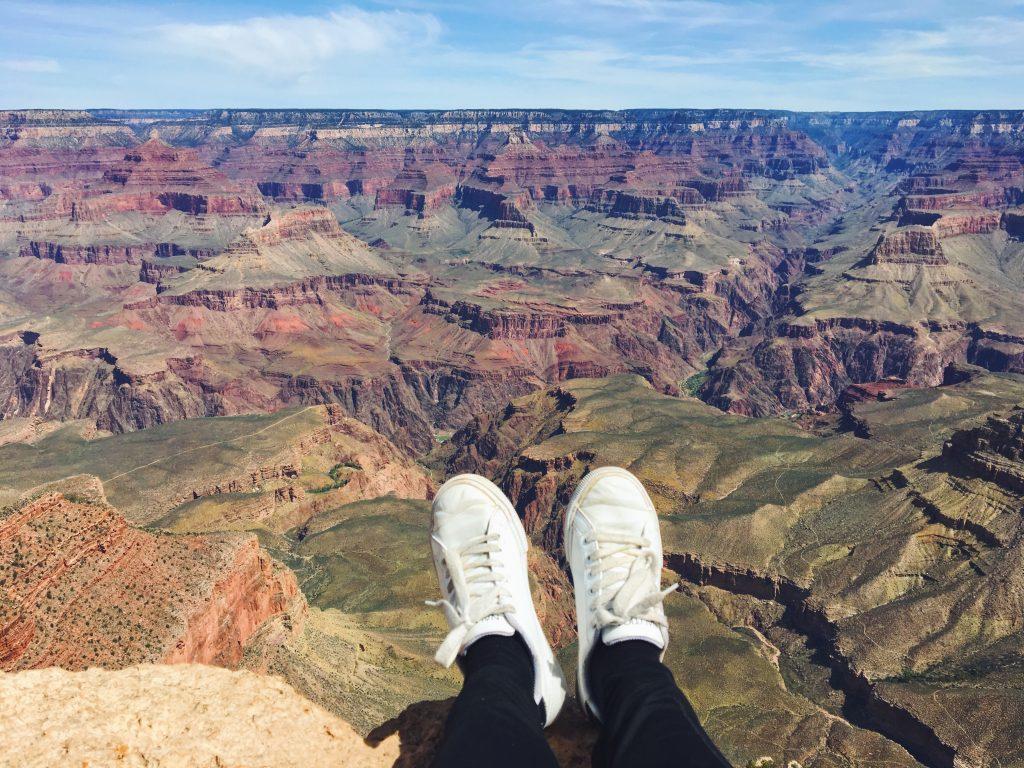 Seduta sul bordo del Grand Canyon