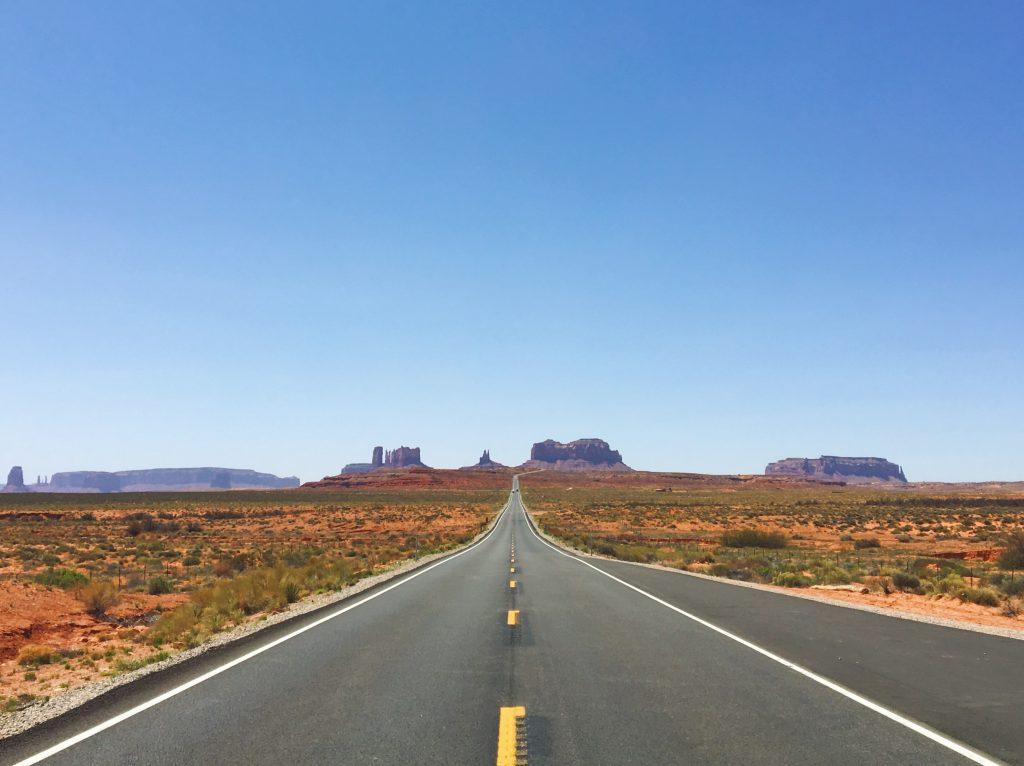 La classica vista da cartolina della Monument Valley con la strada e le rocce di sfondo
